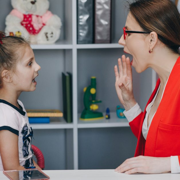 Cute little girl at speech therapist's office. Small child practicing articulation with therapist at private lesson at home.