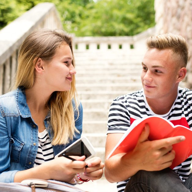 Attractive teenage student couple in front of university studying together.